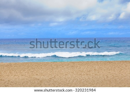 Blue waters and waves on a Hawaiian beach on sunny day - stock photo