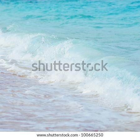 Blue wave on a beach. Shallow DOF. - stock photo
