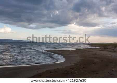 Blue wave on sandy beach after storm - stock photo