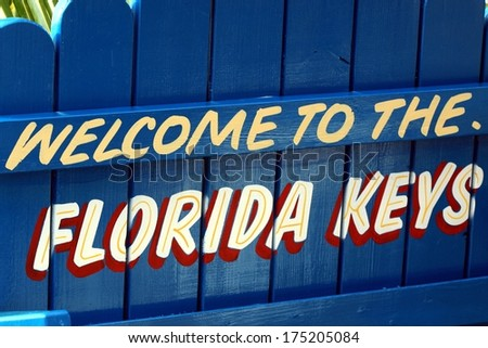 Blue welcome to the Florida Keys sign painted on picket fence - stock photo