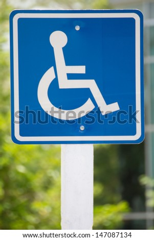 Blue wheelchair sign on the post - stock photo