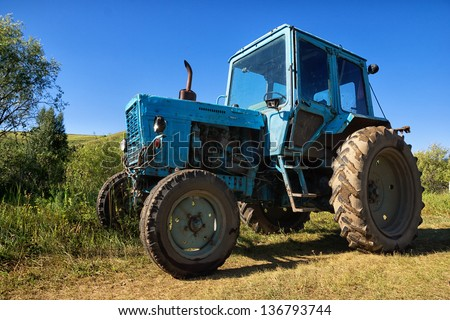Blue wheeled agricultural tractor, dusty and rusty