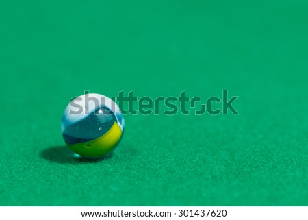 Blue, White and yellow Colorful Marble Ball on Green background - stock photo