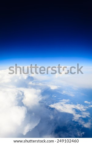 Blue white cloudy sky. View from window of airplane flying in clouds. Skyscape cloudscape. Bird's eye. - stock photo