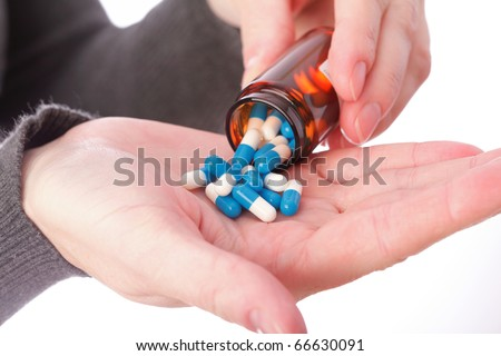 blue - white pills in woman hand isolated - stock photo