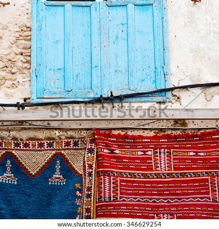 blue window in morocco africa old construction and brown wall red carpet   - stock photo