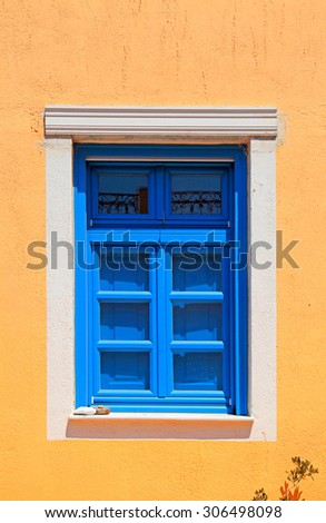 blue window in stone yellow house, Santorini, Greece. - stock photo