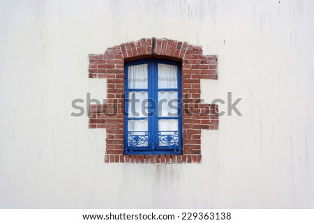 Blue Window metal frame edged with bricks on white House in Brittany, France - stock photo