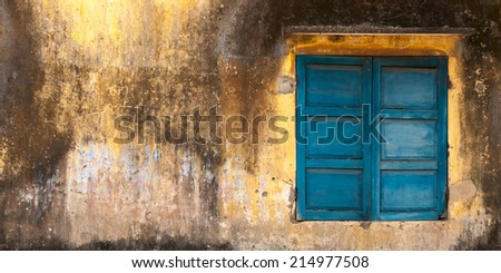 blue window on grunge  yellow wall - stock photo