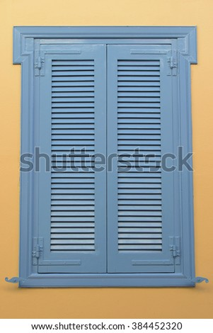 Blue window with wooden shutter and yellow wall background. Architectural detail. - stock photo
