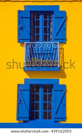 Blue windows on a bright yellow wall of a typical rural house