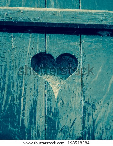 Blue wooden background with carved heart shape. Valentines day background. Toned image.