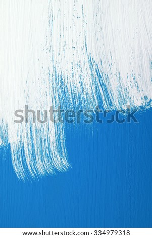 Blue wooden board being roughly painted with a coat of white emulsion paint - stock photo