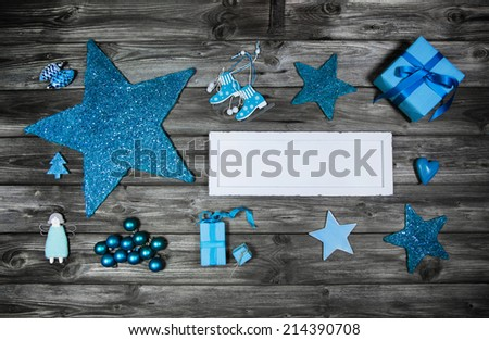 Blue wooden christmas advertising board with decoration on the grey background. - stock photo