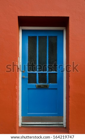 Blue wooden door on a red wall, Reykjavik, Iceland