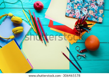 Blue wooden table with education accessories and apple, orange. Top view - stock photo