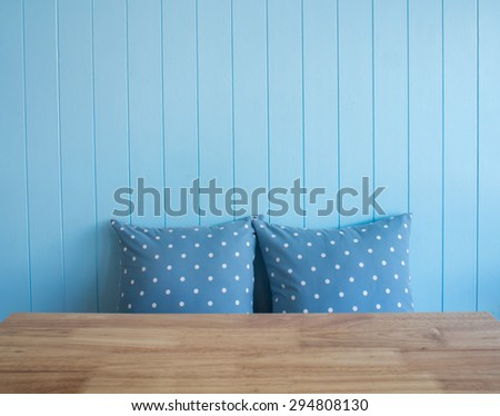 Blue wooden wall background with polka dot pillows and foreground is wooden table  (Composition and space for text) - stock photo