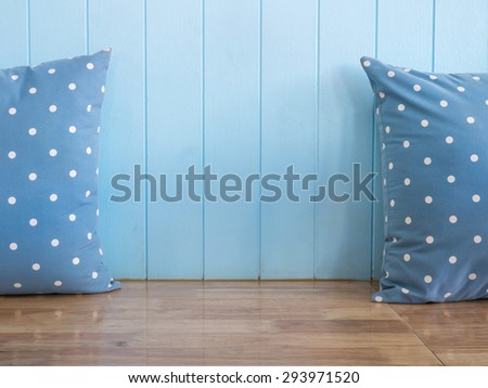 Blue wooden wall background with polka dot pillows on wooden bench (Composition and space for text) - stock photo