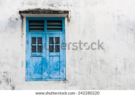 Blue wooden window and grunge wall - stock photo