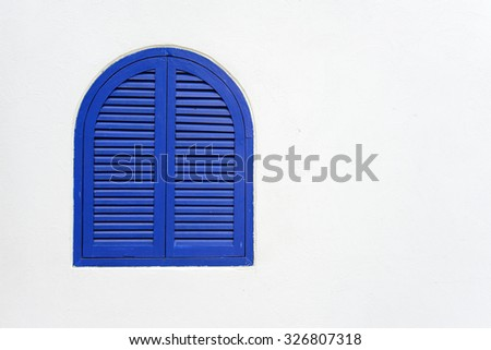 Blue wooden window closed with wooden shutters on white stucco wall with copy space - stock photo
