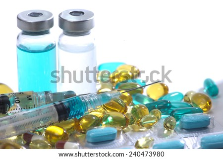 Blue, yellow and red gelatin capsules, glass vials, and syringes. - stock photo
