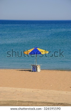 Blue Yellow beach umbrella and deckchair - stock photo