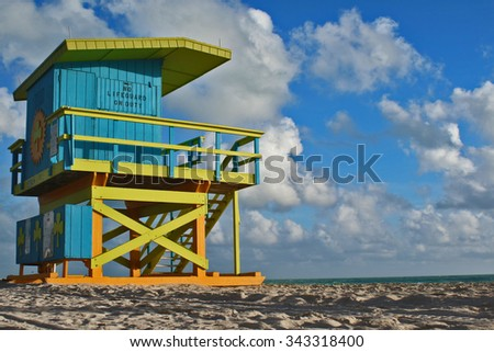 Blue & Yellow Lifeguard station, blue sky with clouds, ocean and sand on a sunny day in Miami, Florida - stock photo