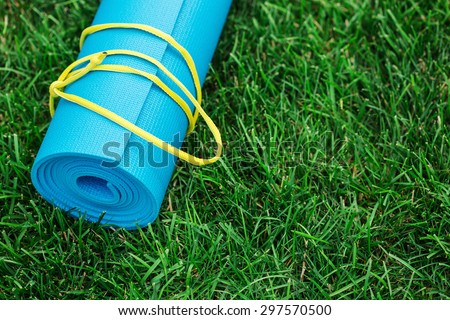 Blue yoga mat on green grass, close up photo, fitness concept - stock photo