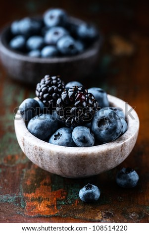 Blueberries and blackberries in small stone dishes - stock photo