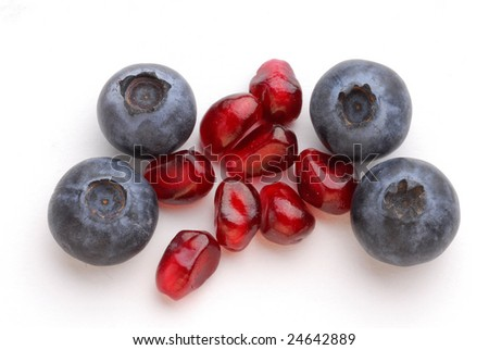 Blueberries and pomegranate very close studio isolated on white background