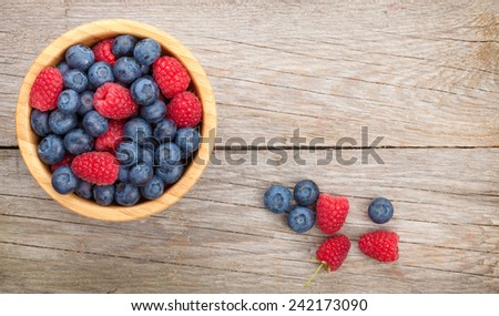 Blueberries and raspberries bowl on wooden table with copy space - stock photo