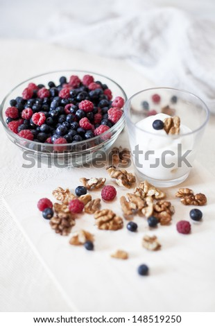 blueberries and raspberries in a bowl on a table next to a glass of sour cream