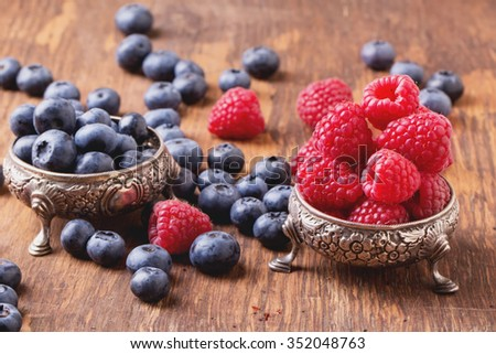 Blueberries and raspberries in two silver fancy bowls on natural rustic wooden board