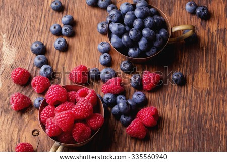 Blueberries and raspberries in vintage copper cups on rustic natural wooden board