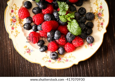 blueberries and raspberries on a plate ventazhnoy wood background. Flat Lay. Top view.