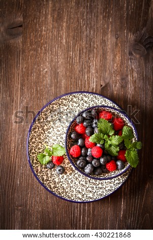blueberries and raspberries on a plate with  black background pattern wood - stock photo