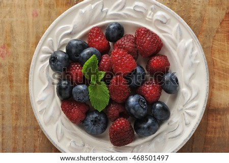 blueberries and raspberries with mint in bowl on wooden background - top view