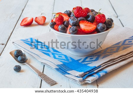 Blueberries and strawberries in White bowl on napkin - stock photo