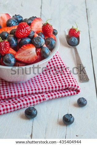 Blueberries and strawberries in White bowl on napkin