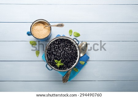 Blueberries in a bowl on a blue table. - stock photo
