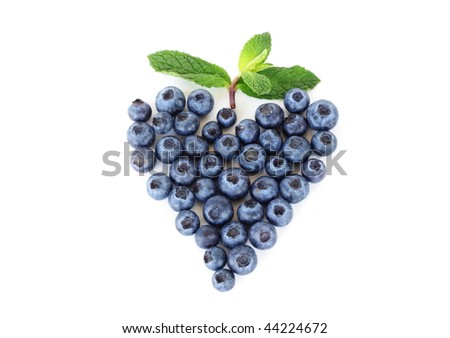 Blueberries in a heart shape with mint leaf - stock photo