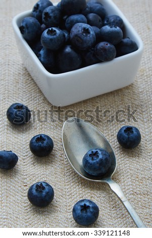 blueberries in a white bowl and on table and spoon