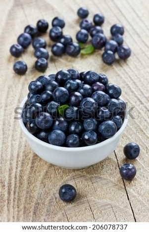 blueberries in a white bowl on a wood rustic background