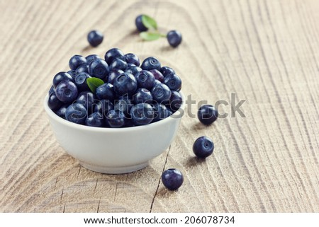 blueberries in a white bowl on a wood rustic background, toned images