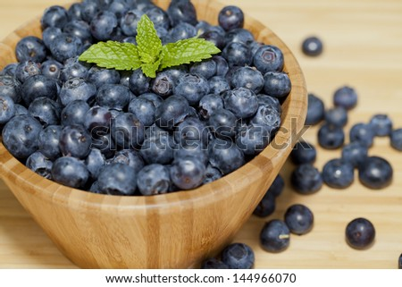 Blueberries in a wooden bowl on a wooden table