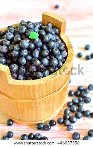 Blueberries in a wooden bucket close-up on a light background