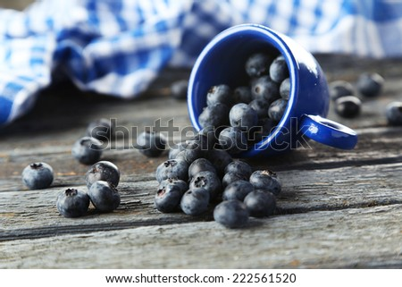 Blueberries in cup on blue wooden background - stock photo