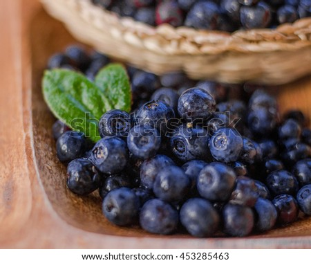 Blueberries in eco wooden plate and basket. Healthy vegan vegetarian dish.