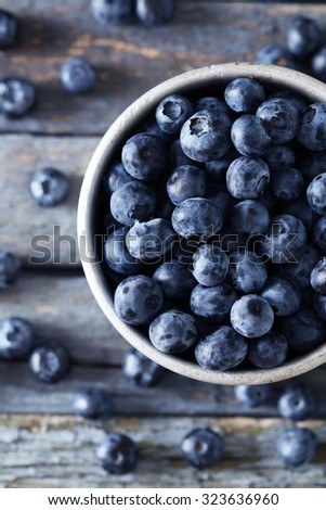 Blueberries in mug on a blue wooden background - stock photo