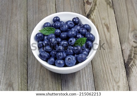 blueberries in porcelain bowl on wooden table